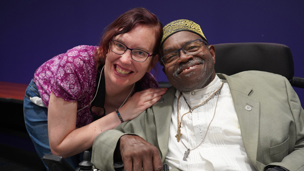 A smiling woman poses next to a smiling man sitting in a wheelchair