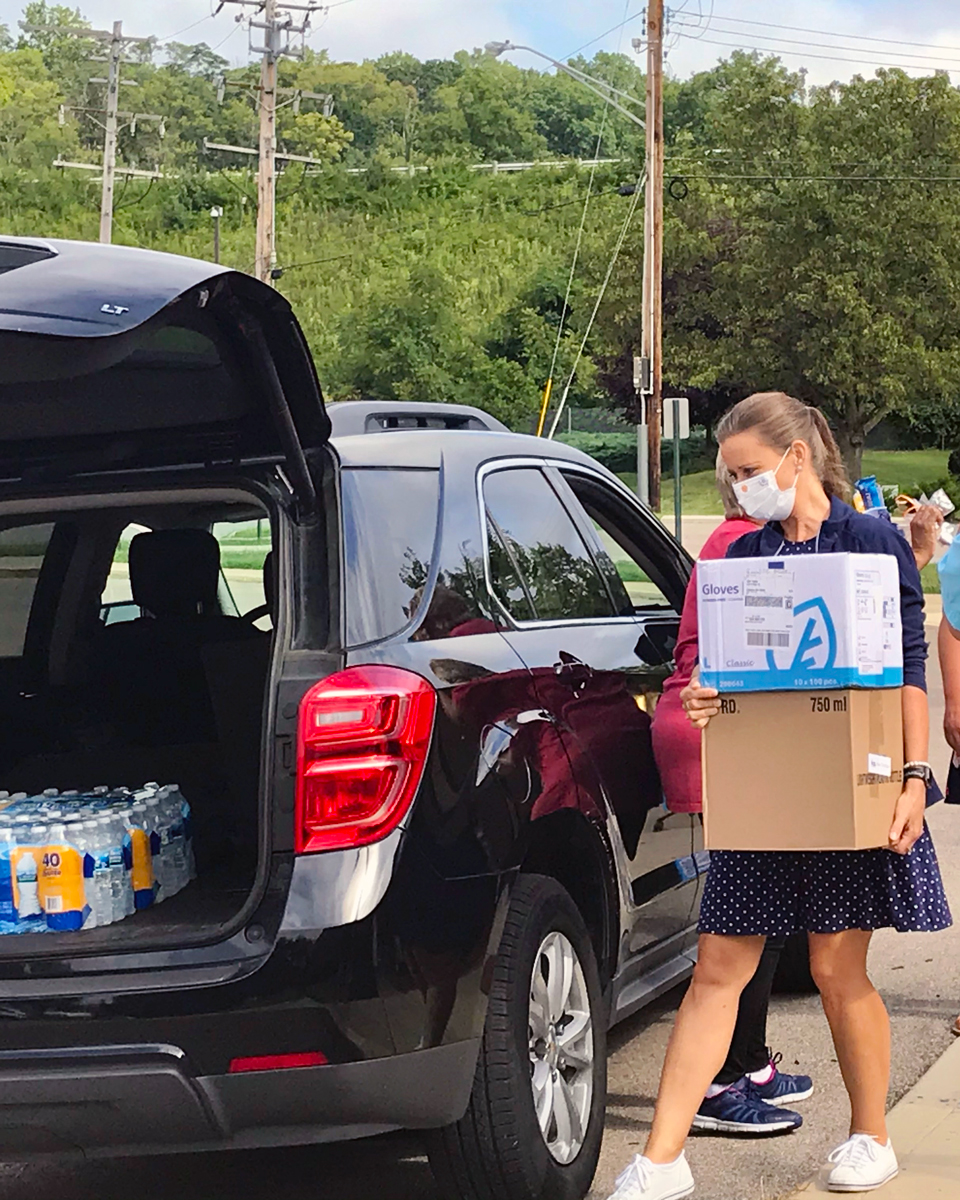 a woman wearing a mask carries boxes of gloves to a car